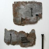 Drift wood, a key and iron nails found in the ground assembled on a white wooden background.