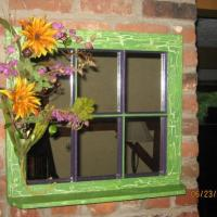 re sanded old window, took glass out and replaced with mirror and added shelf on bottom. Used bright green and a spring cactus green with crackle effect and purple accent along with floral decor