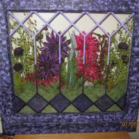 old leaded glass window, re sanded and painted using light and dark purple paint with sponge effect to give texture. Painted some of glass pieces with glass paint. Added shelf on bottom and big silk  flowers behind glass