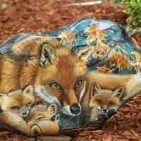 This fox family is painted on a rock weighing 125 pounds. It also displays a beautiful white fox on the back. It has a protective finish.